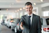 Confident car dealer giving a handshake car showroom on the background poster