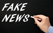 Male hand writing the words Fake News in white text on a blackboard as a reminder to be aware of hoaxes and disinformation for propaganda uses poster