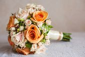 Bridal bouquet with orange and beige roses of different size with handle on white background. Romantic wedding bouquet with beautiful flowers. Elegant round bunch of fresh roses. Accessory of bride poster