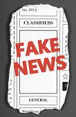 The words Fake News in red text on a white brick wall as a reminder to be aware of hoaxes and disinformation for propaganda uses poster