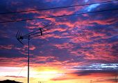 TV antenna over a roof of a family house in a rural area of Spain under wonderful colors of sunset poster