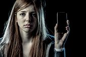 teenager girl or young woman holding mobile phone as internet stalked victim abused in cyberbullying or cyber bullying stress concept and in smartphone and network addiction concept poster