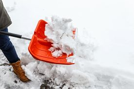 Man with shovel cleaning snow. Winter shoveling. Removing snow after blizzard.