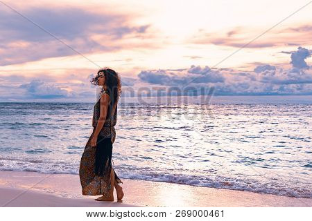Elegant Woman Walking By The Shore Line At The Beach. Sunset And Silhouette