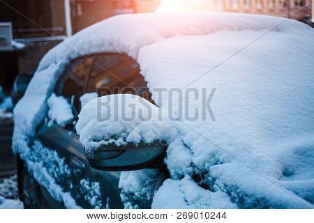 Snow-covered Car. Winter Parking. Rearview Mirror Covered With Snow. Transport After Snowfall.