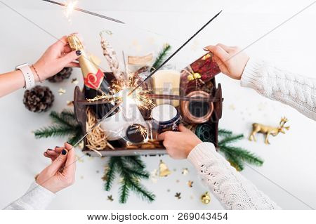 Unrecognizable Women Holding Sparklers And Opening Wooden Basket With Food For Christmas Selebration