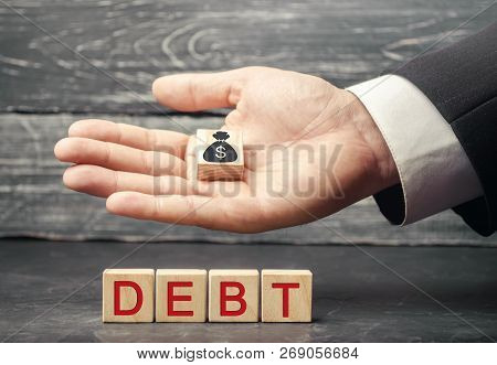 Wooden Blocks With The Word Debt And The Image Of Dollars. Payment Of Taxes And Of Debt To The State