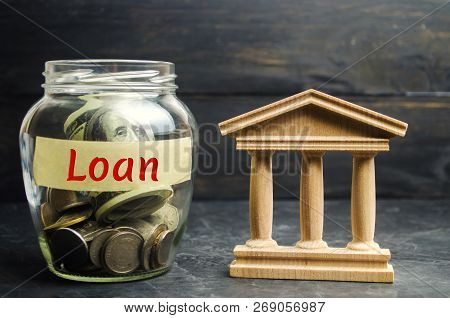 Glass Jar With Coins And The Word Loan And A State Building. Borrow Money, Take A Loan Or A Credit F