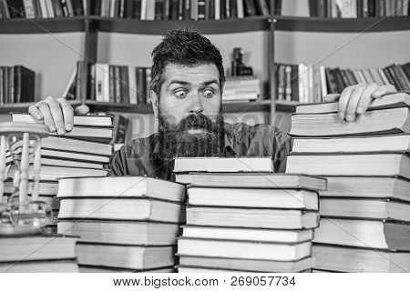 Teacher Or Student With Beard Sits At Table With Books, Defocused. Man On Shocked Face Between Piles