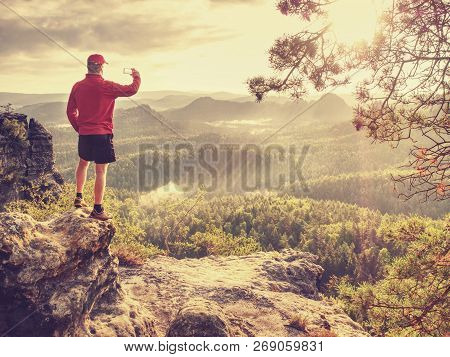 Hiker Is Taking Photo By Smart Phone On The Peak Of Mountain. Man In Red T-shirt And Shorts Takes Ph