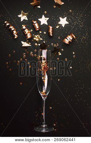 Golden Decoration Of Ribbon, Stars And Confetti Flying From Glass Of Champagne. Flat Lay. Festive Co