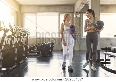 Happy Fitness Couple Senior And Young Woman Holding Yoga Mats And Walking In Class Of Fitness Gym.