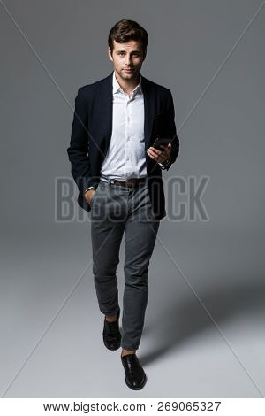 Full length portrait of a confident young businessman dressed in suit isolated over gray background, walking, holding mobile phone