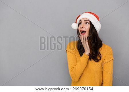 Portrait of joyful woman wearing Santa Claus red hat wondering and looking upward at copyspace isolated over gray background