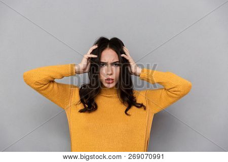 Image of frustrated woman 30s with long dark hair frowning and grabbing head, isolated over gray background poster