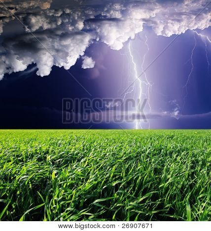 Thunderstorm with lightning in green meadow. Dark ominous clouds.