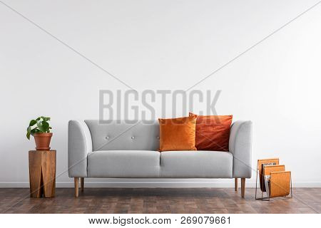 Comfortable Couch With Orange And Red Pillow In Spacious Living Room Interior, Real Photo With Copy