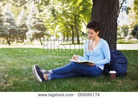 Young Pensive Student Girl Reading Book In The Park, Studying And Preparing For Exams At The Univers