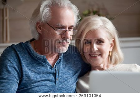 Close Up Of Aged Husband And Wife Relax With Laptop