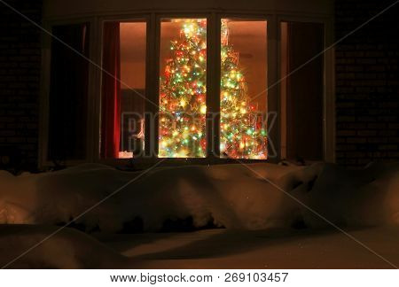 Welcome home Christmas tree in the window background. Night scene with a snow and brightly decorated Christmas tree in a window. Winter Holiday season background,horizontal composition, light blur. poster