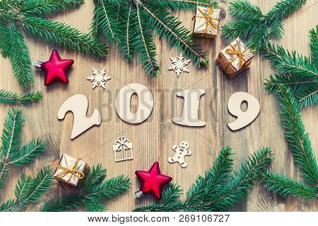 New Year 2019 background with 2019 figures, Christmas toys, blue fir tree branches and snowflakes. New Year 2019 festive seasonal still life in retro tones, festive New Year 2019 composition