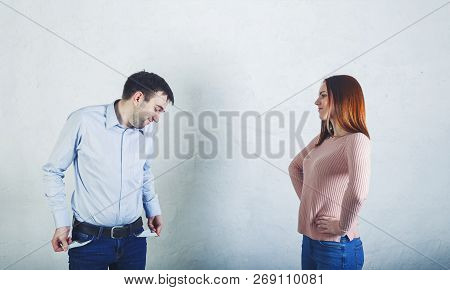 Woman Demanding Money From Her Husband Who Is Showing Empty Pockets On Natural Light Background