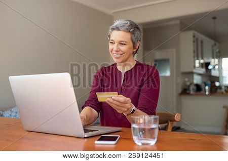 Happy senior woman making online payments of bill using laptop. Smiling mature woman shopping online with credit card. Pensioner holding credit card for internet banking and typing security code.