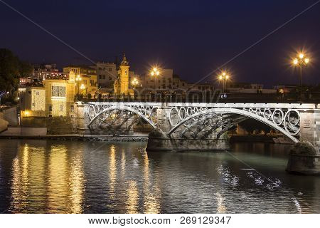 Triana Bridge (isabel Ii Bridge) Over Guadalquivir River At Night, Seville, Spain
