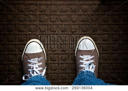 A Dirty Doormat Fills The Image, Looking Down, Feet Wearing Sneakers And Jeans Can Be Seen.