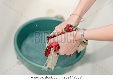 Handwash. A woman is washing her hands. Washing clothes. Wet clothes. poster