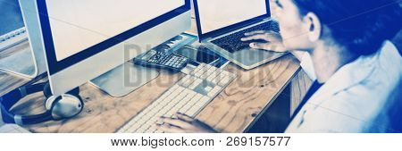 Businesswoman working over computer and laptop in office