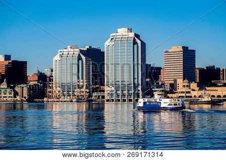 HALIFAX, NOVA SCOTIA, CANADA - AUG 20, 2009: Ferry crossing the harbor while tall ships docked in the early morning on Halifax's waterfront at Purdy's Wharf during the Nova Scotia Tall Ship Festival.