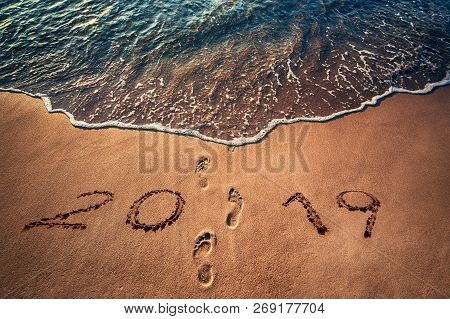 Happy New Year 2019 Concept Written On The Sea Beach At Sunrise