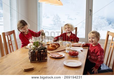Kids Having Breakfast On Christmas Morning. Family Eating Bread And Drinking Milk At Home On Snowy W