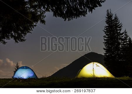Two Brightly Lit Tourist Tents On Green Grassy Forest Clearing On Dark Mountain And Clear Blue Starr