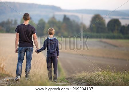 Back View Of Young Father And Son Walking Together Holding Hands By Grassy Field On Blurred Foggy Gr