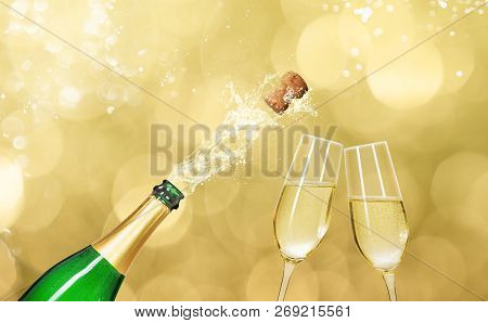 A Champagne Bottle With Two Champagne Glasses