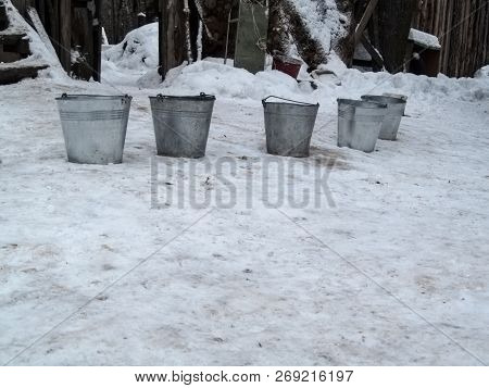 Five Metal Buckets Stand On The Snow In A Rural Yard. Creative Winter Rural Background With Copy Spa