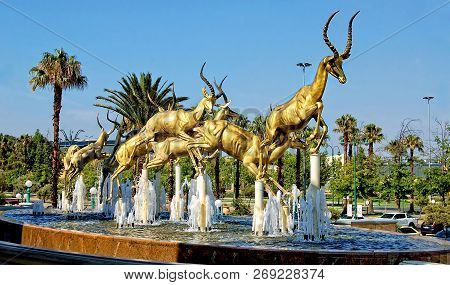 Gold. Mining Industry Of South Africa. Amazing Golden Springboks Jump In A Fountain With Blue Sky In