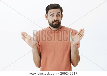 Waist-up Shot Of Worried Unaware And Clueless Charming Man With Beard Raising Palms And Shrugging Lo