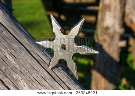 Shuriken (throwing star), traditional japanese ninja cold weapon stuck in wooden background poster