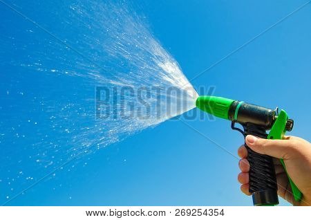 Hand With Water Spray Jet Against The Blue Sky