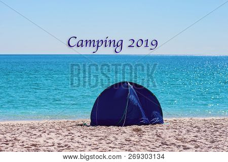 Camping 2019 Caption Text.  A Small Blue Round Collapsible Shade Tent On The White Silica Sand Of Wh