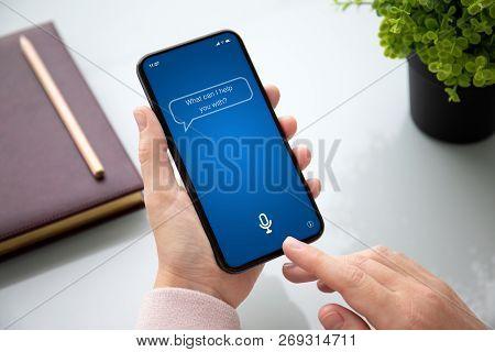 Female Hand Holding Touch Phone With App Personal Assistant On Screen Above The Table In The Office