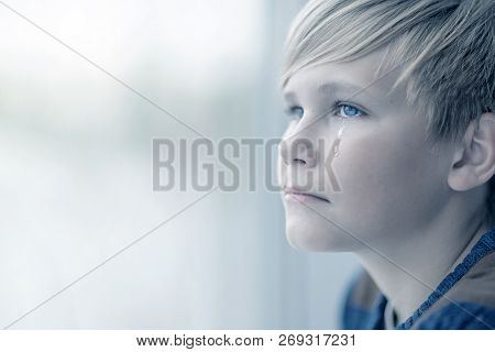 Crying Boy Looks Out The Window. Portrait Of Sad Blond Teen 12-14 Year Old
