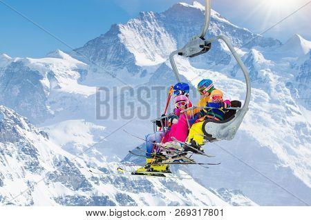 Family In Ski Lift In Mountains. Skiing With Kids