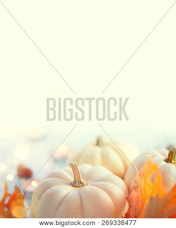 Thanksgiving Day Dinner, Served holiday table decorated with pumpkins, colorful autumn leaves and candles. Thanksgiving background, beautiful table setting. Vertical image