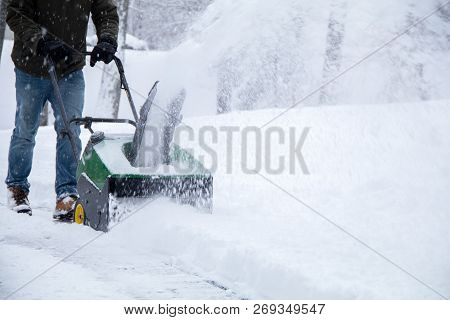 Snowblower In Action During A Snowstorm In The Northeast, Maintaining Driveway During Storm