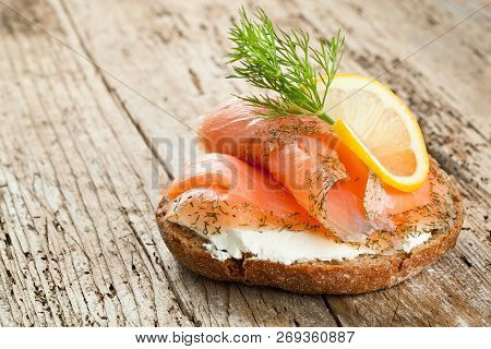 Bread With Fresh Salmon Fillet Isolated On Wooden Background.