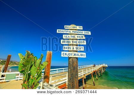 Malibu, California, United States - August 7, 2018: Paradise Cove Pier Sign And Wooden Jetty In Para